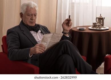 Elder man reading old letter and smoking cigar