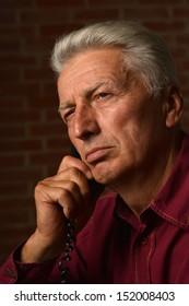 elder man in a shirt on a brick background