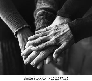 Elder people holding hands together black and white