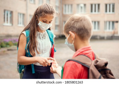 Elder sister applying sanitizing gel at hands of her small brother first-grader near the school before returning home after classes