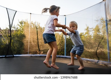 Elder sister holding hands of her brother and jumping