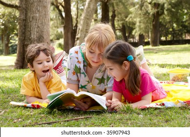 Elder sister reads to children of the book on a glade in park