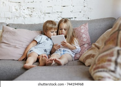 Elder sister relaxing on couch in living room with her little brother and watching cartoon series online on electronic device while parents are busy. Cute boy and girl using digital tablet at home