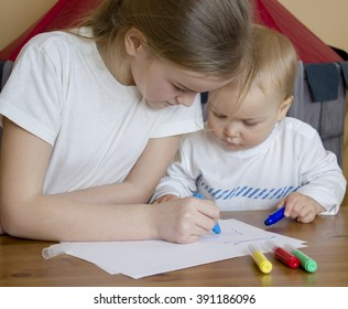 Elder sister teaches the brother to draw felt-tip pens on paper. Entertainment for different age