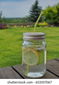 Elder syrup, water, slice of lemon and elder flower in glass with green straw.