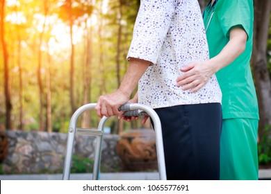 elder with walker in garden