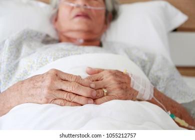 elder wearing oxegen mask in hospital
