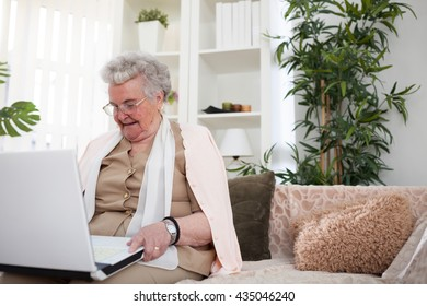 Elder well-dressed woman spending time on laptop in her home
