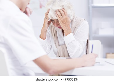 Elder woman alarmed by her health state, sitting in a doctor's office