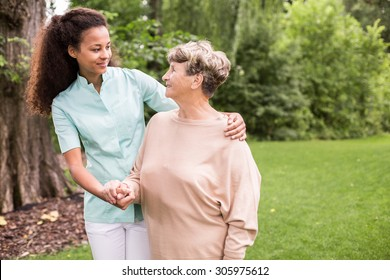 Elder woman and caregiver walking in the park