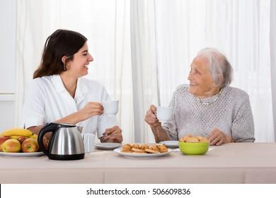 Elder Woman Enjoying Tea With Her Caretaker
