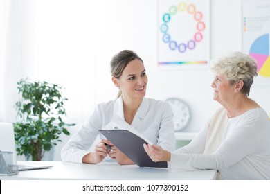 An elder woman holding a diet plan during her diet consultation with a young doctor