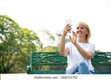 elder woman holding mobile phone in garden
