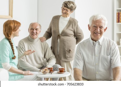 Elder woman holds hand on shoulder of husband while talking with nurse