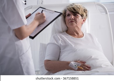 Elder woman in hospital bed talking to her doctor