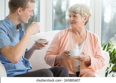 Elder woman and male nurse drinking coffee