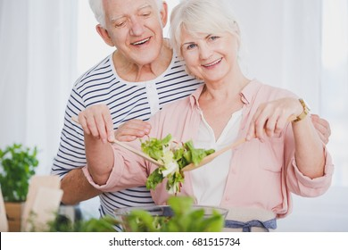 Elder woman and man preparing salad in the kitchen together