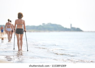 Elder Woman nordic walking on the beach old