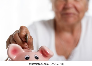 Elder woman putting pin money coins into pink piggybank slot. Budgeting expenses concept. Making savings and effective investment concept. Future needs deposit. Focus on coin. Retirement problems
