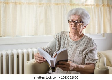 Elder woman reading a book at home.