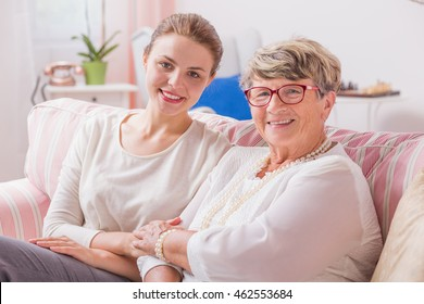 Elder woman sitting on a couch with her young granddaughter