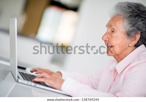 Elder woman using a computer and looking very happy