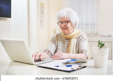 Elder woman using a laptop computer at home.