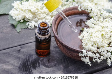 Elderberry essential oil or extract of tincture with elderberry flowers on a wooden background. The concept of alternative medicine.