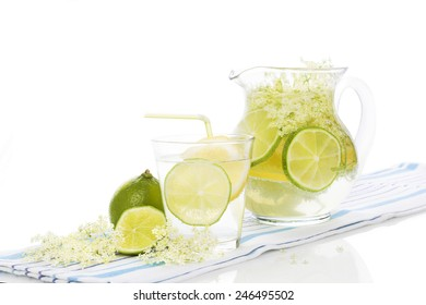 Elderberry lemonade with fresh lemon and lime and elderberry blossom isolated on white background. Fresh summer healthy drink.