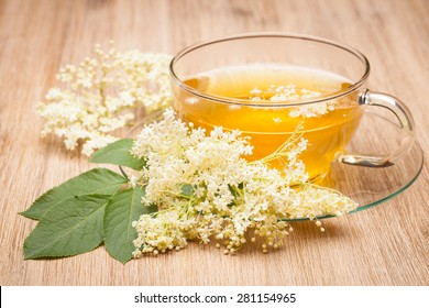 Elderberry (Sambucus nigra) Holunderbl�¼tentee on wooden table