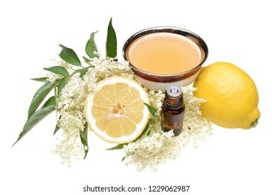Elderflower branch with lemon, tea and oil isolated on white background