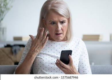 Elderly 50s woman sitting on couch in living room holding smart phone gesturing looking annoyed feels angry having problem with gadget, slow internet, connection lost, discharged broken device concept