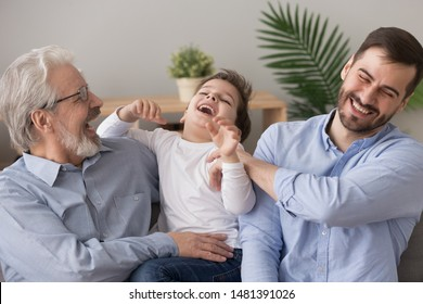 Elderly 60s grandpa and grown up son tickling small adorable boy, cheerful family multi generational men having fun laughing feels happy sitting on couch at home, leisure activities love care concept