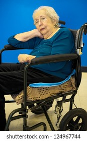 Elderly 80 plus year old woman portrait with a blue background.