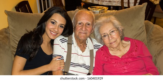Elderly 80 plus year old grandparents with granddaughter in a home setting.