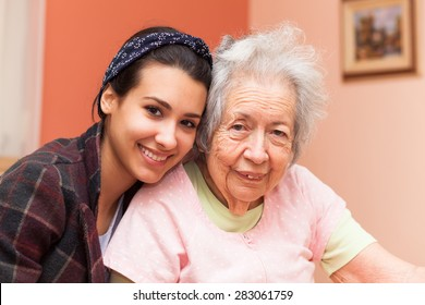 Elderly 80 plus year old grandmother with granddaughter in a home setting.