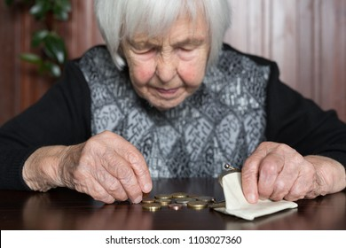 Elderly 95 years old woman sitting miserably at the table at home and counting remaining coins from the pension in her wallet after paying the bills.
