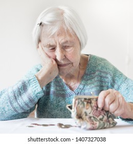 Elderly 96 years old woman sitting miserably at the table at home and counting remaining coins from pension in her wallet after paying bills. Unsustainability of social transfers and pension system.