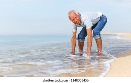 Elderly active man checks the water temperature on the beach