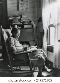 Elderly African American woman writing in a rocking chair, Putnam, Georgia, May 1941.