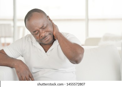 Elderly african man suffering from neck pain at home on couch. Males sense of fatigue, exhausted, stressed. African man massages her painful neck with her hands. The concept of body and health.