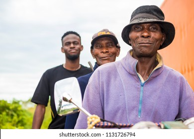 elderly african man wearing a hat and sitting on a motorcycle and two other people behind him. elderly nigerian man sitting on an okada and two people behind him