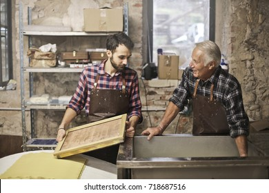 Elderly artisan and young apprentice at work