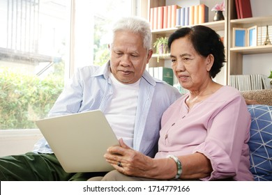An elderly Asian couple sitting on a sofa watching media online on a laptop In the living room at home Both are happy in life after retirement. Concept of health insurance, Social distance
