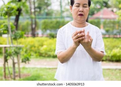 Elderly asian female with beriberi on hand or finger,Disease causing inflammation of the nerves