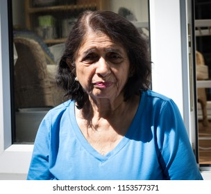Elderly Asian lady sat in the back garden