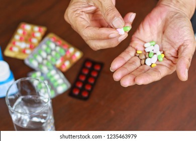 Elderly Asian man holding many pills(tablet and capsule) in hands and pick some medicines for taking, supplements or antibiotic antidepressant painkiller medication Hope for cure,Top up view.