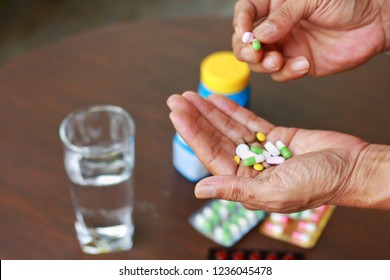 Elderly Asian man holding many pills(tablet and capsule) in hands and pick some of medicine,supplements or antibiotic antidepressant painkiller medication.Hope for cure,closeup view.