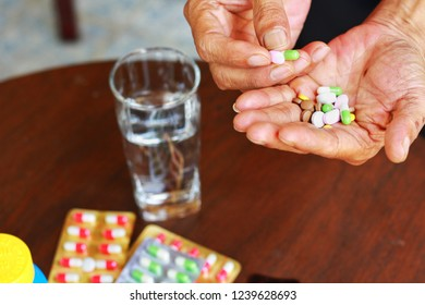 Elderly Asian man holding many pills(tablet and capsule) in hands and pick some medicines for taking, supplements or antibiotic antidepressant painkiller medication Hope for cure,Flat lay.