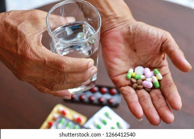 Elderly Asian man holding many pills (tablet,capsule ) and glass of water in hands.Taking a lot of medicine, supplements ,antibiotic antidepressant or painkiller medication.Hope for cure,Top view.